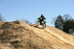 Businessman on Dirt Bike. Thrity something business man in suit riding dirt bike on dirt riding track Royalty Free Stock Photo