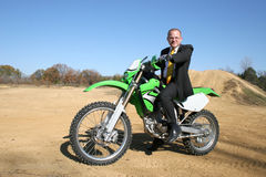 Businessman on Dirt Bike. Thrity something business man in suit riding dirt bike on dirt riding track Stock Photo