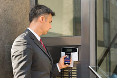 Businessman Disarming Security System Of Door With Smartphone Royalty Free Stock Photo