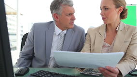 Businessman discussing a document with his colleague. In an office stock video footage