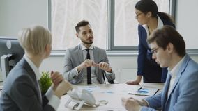 Businessman discussing future business project with male and female colleagues sitting at the table in modern office. Indoors