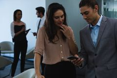 Businessman discussing with his coworker over mobile phone royalty free stock photo