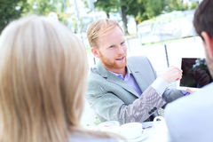 Businessman discussing over digital tablet with colleagues at sidewalk cafe Stock Photos
