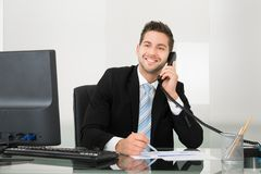 Businessman discussing over documents on telephone at desk Royalty Free Stock Image