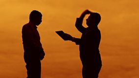 Businessman discussion sunset evil boss silhouette sunlight standing clipboard concept. two businessman men swearing. Outdoors conflict fight looking slow stock footage