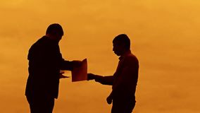 Businessman discussion sunset silhouette sunlight evil boss standing clipboard concept. two businessman men swearing. Outdoors conflict fight looking slow stock footage