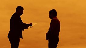 Businessman discussion sunset silhouette sunlight standing clipboard concept. evil boss two businessman men swearing. Outdoors conflict fight looking slow stock video footage
