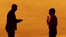 Businessman discussion sunset silhouette sunlight standing clipboard concept. evil boss two businessman men outdoors. Swearing conflict fight looking slow stock video
