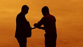 Businessman discussion sunset silhouette sunlight standing clipboard concept. two businessman men shake hands meeting. Are in talks looking outdoors slow motion stock footage