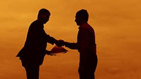 Businessman discussion sunset silhouette sunlight standing clipboard concept. two businessman men shake hands meeting. Are in talks outdoors looking slow motion stock video