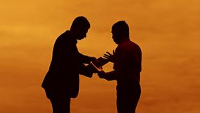 Businessman discussion sunset silhouette sunlight standing clipboard concept. two businessman men are in talks looking. Outdoors slow video stock footage