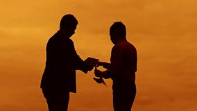 Businessman discussion sunset silhouette sunlight standing clipboard concept. two businessman men are in talks looking. Businessman discussion sunset silhouette stock video footage