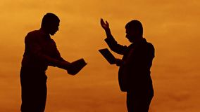 Businessman discussion sunset silhouette sunlight standing clipboard concept. two businessman men swearing outdoors. Conflict fight looking slow motion video stock footage