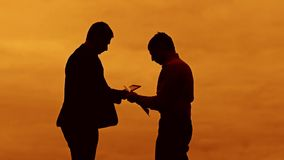 Businessman discussion sunset silhouette sunlight standing clipboard concept. two businessman men are in talks looking. Slow video stock footage