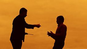 Businessman discussion sunset silhouette sunlight standing evil boss clipboard concept. two businessman men swearing. Outdoors conflict fight looking slow stock video