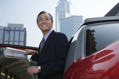 Businessman Disembarking From Cab Stock Photography