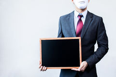 Businessman in disguise mask holding blackboard sign Stock Photo