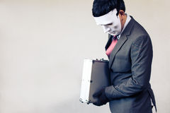 Businessman in disguise mask stealing a confidential suitcase - with copyspace.  Stock Photo