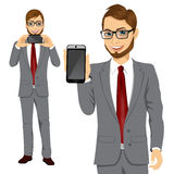 Businessman displaying his smartphone. Portrait of young attractive businessman displaying his smartphone on horizontal and vertical position Stock Images