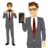 Businessman displaying his smartphone. Portrait of young attractive businessman displaying his smartphone on horizontal and vertical position Royalty Free Stock Images