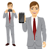 Businessman displaying his smartphone. Portrait of young attractive businessman displaying his smartphone on horizontal and vertical position Stock Photography