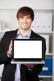 Businessman Displaying Laptop In Office Royalty Free Stock Photo
