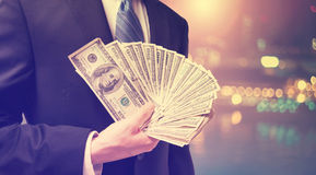 Businessman displaying spread of cash. On blurred city background Royalty Free Stock Images