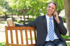 Businessman with disposable cup answering cellphone Royalty Free Stock Photo