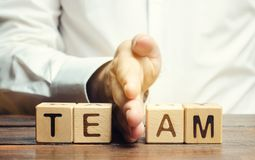 A businessman divides the word Team into two parts. Small grouping. Employee management. Working staff. The organization of the. Team. The division of work stock images