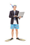 Businessman with diving equipment holding laptop Stock Photos