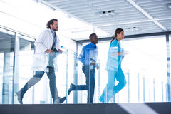Businessman, doctor and nurse in hospital corridor Royalty Free Stock Images