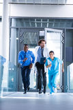 Businessman, doctor and nurse in hospital corridor. During emergency stock photography