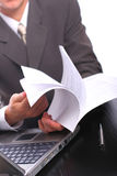 Businessman with documents. The businessman looks through documents sitting for a table stock photography