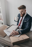 Businessman with documents and folders drinking coffee and sitting at table in office Royalty Free Stock Photo