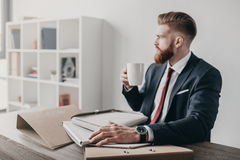 Businessman with documents and folders drinking coffee and sitting at table in office Stock Images