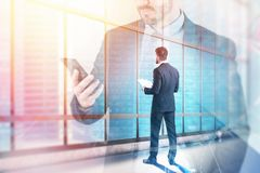 Man with documents looking at city. Businessman with documents looking at city through panoramic office window with double exposure of businessman with stock images
