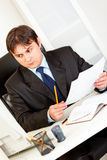 Businessman with documents sitting at office desk Stock Images