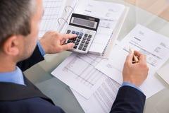 Businessman doing calculating Stock Photo