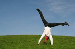 Businessman doing cartwheel. Young businessman doing cartwheel outdoors Stock Photography