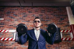 Businessman doing dumbbell biceps wearing formal suit. A businessman doing dumbbell biceps curl wearing a formal suit. Conceptual of Business strength Stock Images