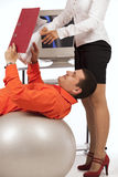 Businessman doing exercise with ball. Smiling businessman doing exercise with a grey workout ball , over white background. His secretary, showing files with Royalty Free Stock Photography