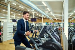 Businessman doing exercises on the simulator in the gym Royalty Free Stock Photography
