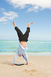 Businessman doing handstand on the beach Stock Photo