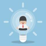 Businessman doing meditation inside light bulb. Idea concept Stock Images