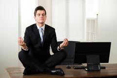 Businessman Doing Meditation In Office Royalty Free Stock Photos