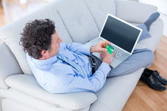 Businessman doing online shopping on couch Stock Photography