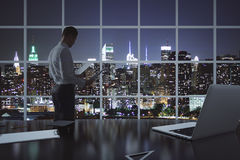 Businessman doing paperwork. In office with laptop, clipboard and other items on desktop. Window with illuminated night city view in the background. 3D Stock Photos