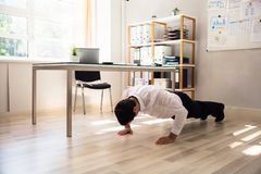 Businessman doing push up. On hardwood floor in office royalty free stock image