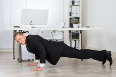 Businessman Doing Pushup At Work Stock Image