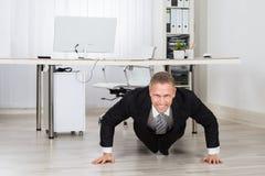 Businessman Doing Pushup At Work Stock Photos